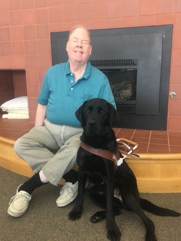 Mike and his new guide dog Alamo in front of the fireplace